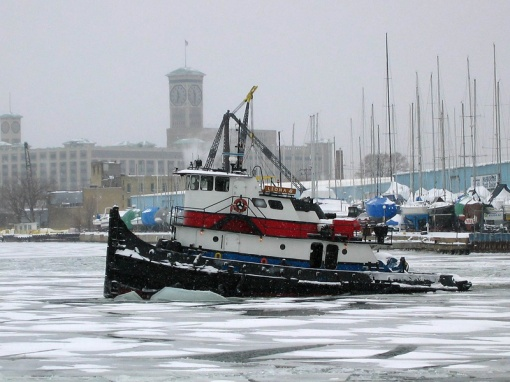 The ice breaker is breaking up ice in Milwaukee harbor during a snow storm