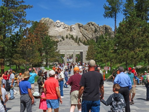 Crowds enter and look in awe at the entrance to the Mount Rushmore National Memorial.